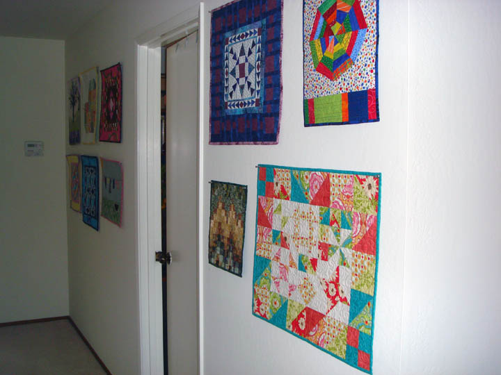 Mini quilts on hallway wall