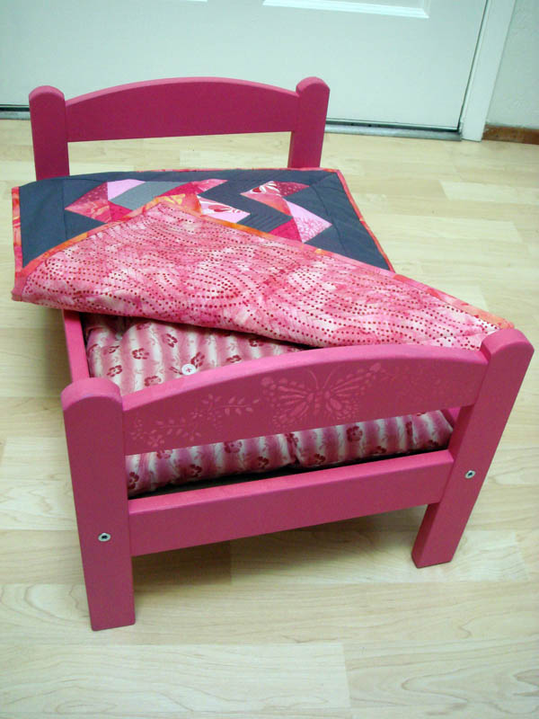 Pink doll bed with zig zag quilt
