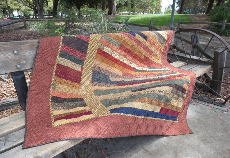 Moda Troubles jelly roll quilt on bench